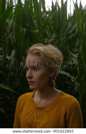 blonde woman standing in a corn field