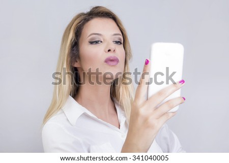 Blonde woman taking a photo of herself on a cell phone  - stock photo