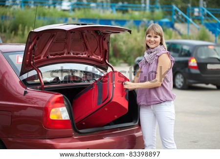 Blonde woman taking off suitcases from the car trunk - stock photo