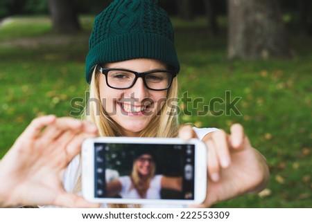 Blonde woman taking self portrait, selfie concept - stock photo
