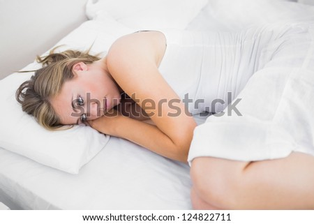 Blonde woman thinking in the bed in the white background