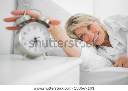 Blonde woman turning off ringing alarm clock lying in bed at home - stock photo