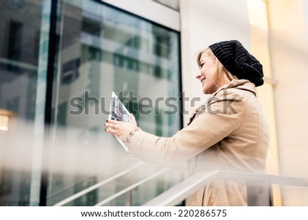 Blonde woman using a digital tablet outdoor