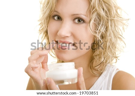 Blonde woman using lotion - stock photo