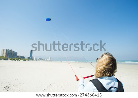 Blonde woman wearing a backpack flying a kite at the sandy sunny beach