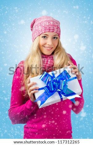 blonde woman wearing knitwear  holding gift box over blue background with snow - stock photo