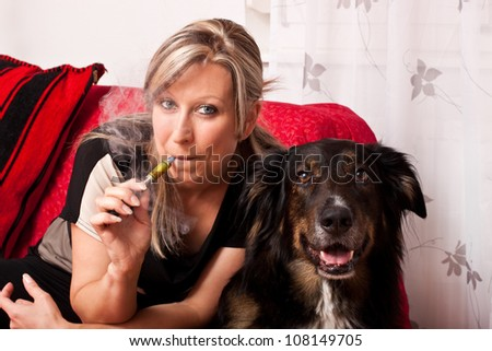 Blonde woman with a dog smoking a e cigarette - stock photo