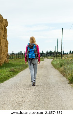 Blonde woman with backpack and binoculars enjoys walking the country road,Walk the country road