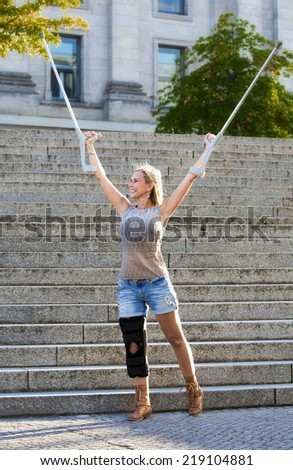 blonde woman with crutches standing in front of stairs - stock photo