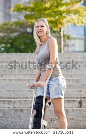 blonde woman with crutches standing on stairs - stock photo