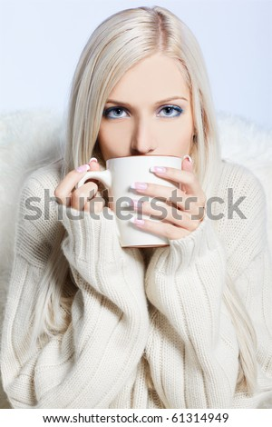 blonde woman with cup of hot coffee or tea - stock photo