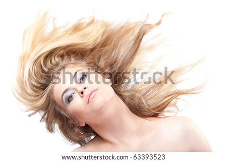 Blonde woman with her hair blowing looking at camera - stock photo