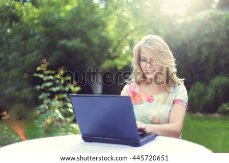 Blonde woman with notebook at the table in the garden