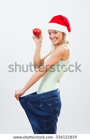 Blonde woman with Santa hat holding apple.Fit for holidays - stock photo