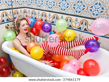 Blonde woman with sunglasses playing in her bath tube with bright colored balloons. Sensual girl with white and red striped stockings having fun in bathroom, covered with balloons  - stock photo