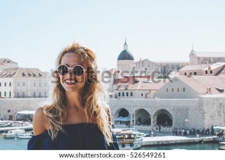 Blonde woman with sunglasses smiling in front of Dubrovnik city walls