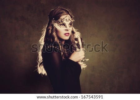blonde woman with venetian mask and glass of champagne studio shot  - stock photo