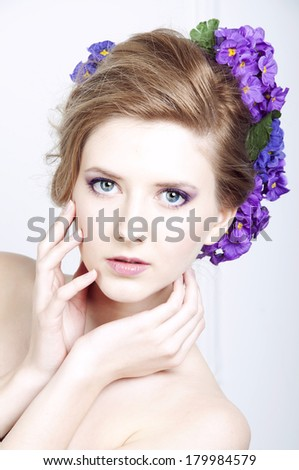Blonde young caucasian woman with violet flowers in her hair - stock photo