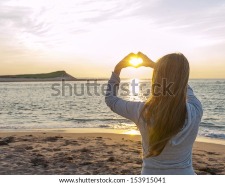 Blonde young girl holding hands in heart shape framing setting sun at sunset on ocean beach - stock photo