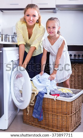 Blonde young housewife and little girl doing laundry together - stock photo