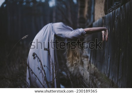 Blonde young model in a lavender maxi dress bends back in a creepy unnatural way in the dark forest