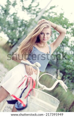 blonde young sexy woman having fun cycling on country road & looking at camera under bright summer sky and green outdoors copy space background, portrait