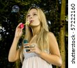 blonde young woman blowing soap bubbles in summer day - stock photo