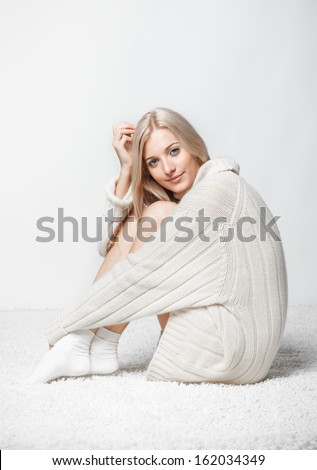 Blonde young woman dressed in long white cashmere sweater sitting on white whole-floor carpet and gray background - stock photo