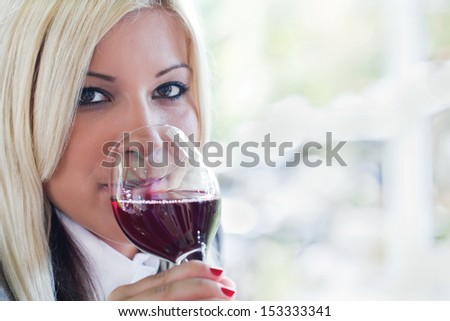 blonde young woman drinking red wine