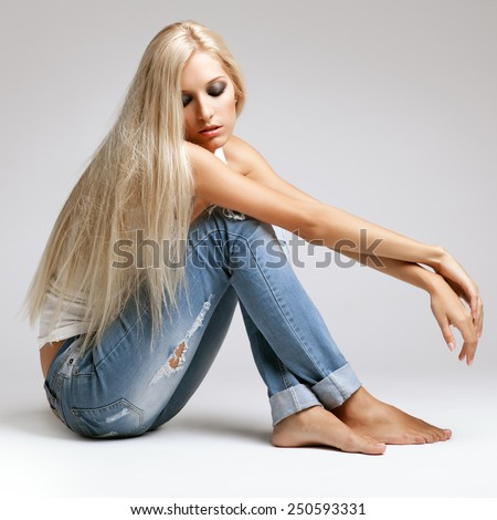 Blonde young woman in ragged jeans and vest sitting on floor on gray background