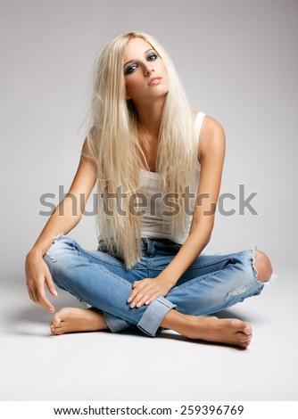 Blonde young woman in ragged jeans and vest sitting on floor on gray background - stock photo
