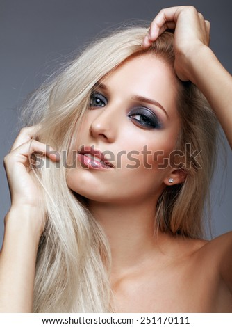 Blonde young woman on gray background - stock photo