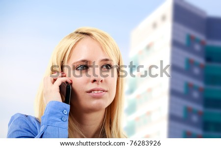 Blonde young woman on the phone with a glass building in the background
