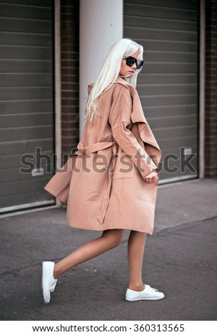 Blonde young woman posing outdoors - stock photo