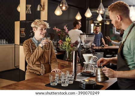 Blonde young woman sitting at the counter of a modern coffee shop with a cup of coffee, smiling while listening to the barista talking and making filter coffees - stock photo