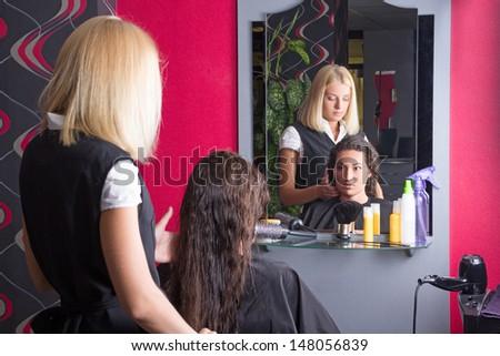 blondie hairdresser and brunette customer in beauty salon - stock photo