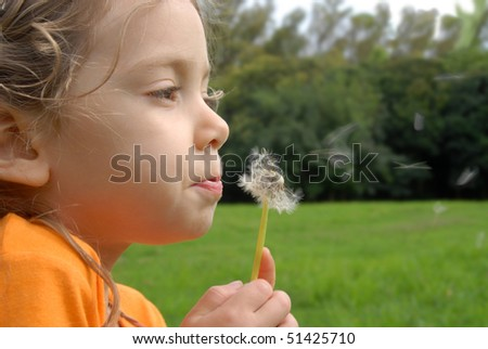 Blondie little girl playing with flying dandelion seeds