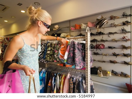 Blong girl buying clothes in a shop - stock photo