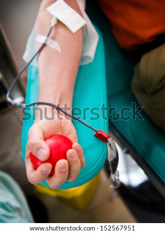 Blood donor at donation with a bouncy ball holding in hand. - stock photo