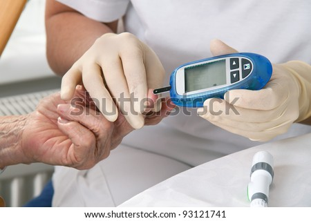 blood glucose meter. the blood sugar value is measured on a finger - stock photo
