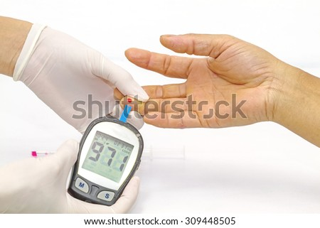 blood glucose meter, the blood sugar value is measured on a finger by  female doctor in white medical gloves - stock photo