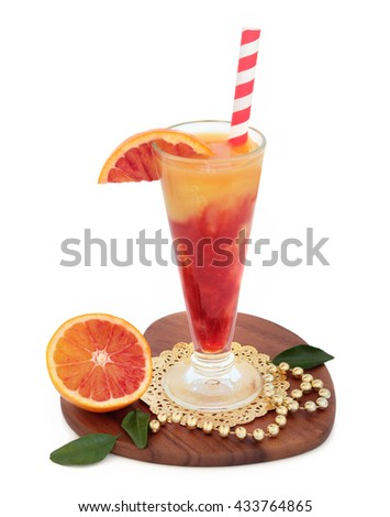 Blood orange juice drink with fresh fruit on a gold doilie with bead decoration on a heart shaped maple wood board over white background. High in vitamins, anthocyanins and antioxidants. - stock photo