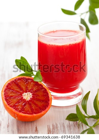 blood orange juice in glass with halved blood orange on the wooden table - stock photo