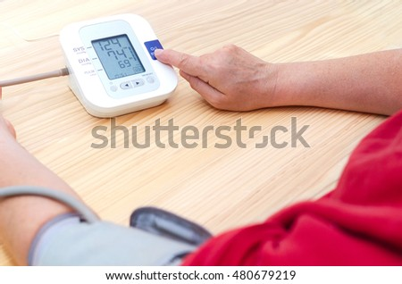 Blood pressure digital pulse monitor. Woman measuring her blood pressure and hearth rate. Health.