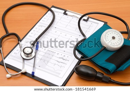 Blood pressure measurement and ECG curve - stock photo