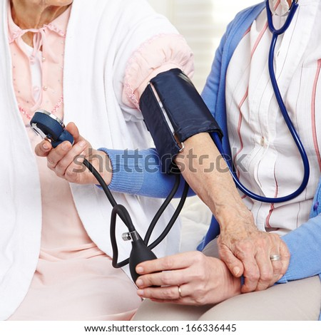 Blood pressure measurement in nursing home on senior woman - stock photo