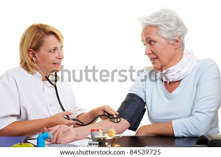 Blood pressure measurement of senior woman at doctor - stock photo