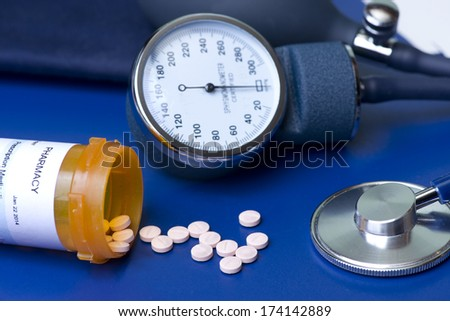 Blood pressure medication, cuff, and stethoscope. - stock photo