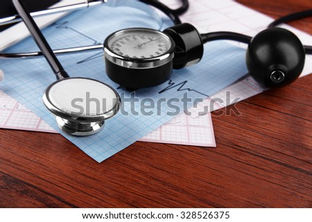 Blood pressure meter and stethoscope, on wooden background - stock photo