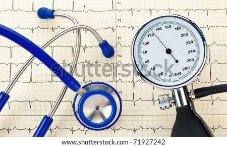 Blood pressure monitor, stethoscope and ECG curve. Correct blood pressure measurement. - stock photo